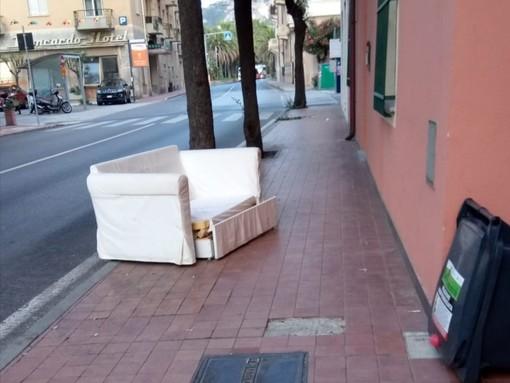 Divano abbandonato in mezzo al marciapiede in pieno centro: l'immagine tra stupore e indignazione