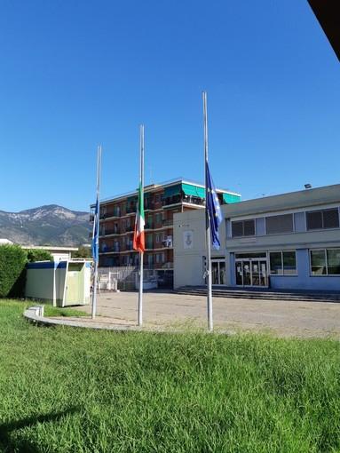 Le bandiere a mezz'asta davanti al palazzo comunale di Borghetto Santo Spirito