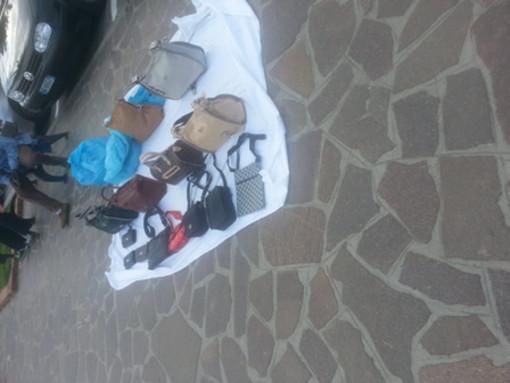 Borse di gran marca (ma false) in spiaggia a Finale Ligure