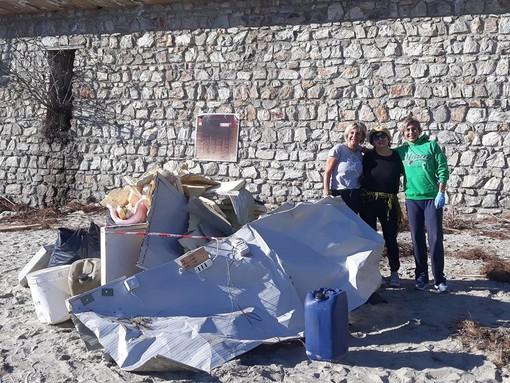 Finale Ligure: tre volontarie ripuliscono la spiaggia del porto di San Donato
